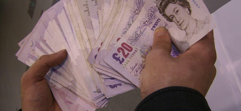 przedsiębiorca trzymający w rękach wiele funtów brytyjskich